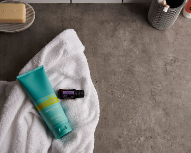 doTERRA Spa Hand and Body Lotion with Lavender Peace essential oil blend and bathroom accessories on a white towel on a stone background.