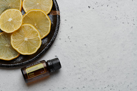 doTERRA Lemon oil and slices on black ceramic plate with white concrete background.