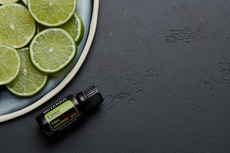doTERRA Lime oil and lime slices on blue ceramic plate with black concrete background.