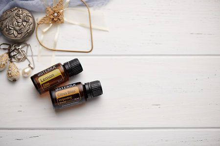 doTERRA Lemon and Citrus Bliss oils with romantic jewellery on a white vintage wooden background.