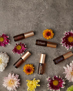 doTERRA Precious Florals Collection featuring Neroli Touch, Jasmine Touch, Rose Touch, Magnolia Touch and Blue Lotus Touch with flowers on a gray stone background.