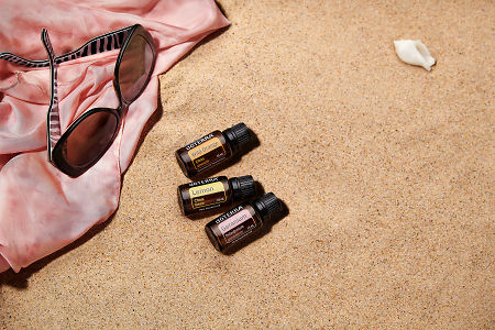 doTERRA Wild Orange, Lemon and Geranium with sunglasses and a pink silk scarf on the beach.