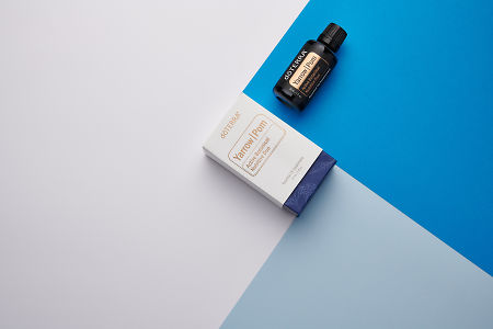 doTERRA Yarrow Pom and product box on royal blue, light blue and white geometric background.