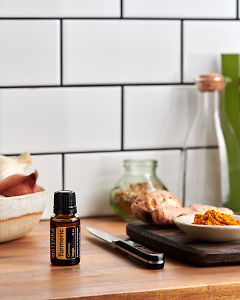 doTERRA Turmeric on a kitchen bench with fresh and ground turmeric.