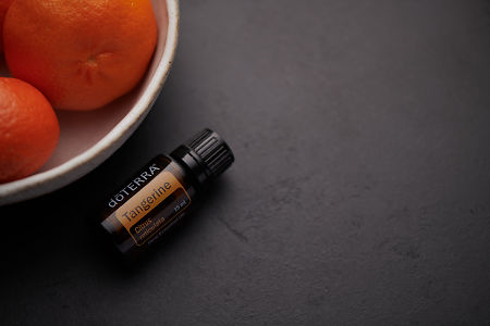 doTERRA Tangerine oil and fruit in white ceramic bowl on black background.