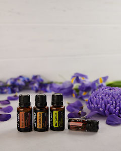 doTERRA Frankincense, Wild Orange, Bergamot and Cinnamon Bark with scattered purple flowers on white.