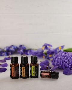 doTERRA Frankincense, Wild Orange, Bergamot and Cinnamon Bark with scattered purple flowers on white.