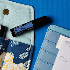 doTERRA Ice Blue Touch on an essential oil bag with a diary on a blue textured background.