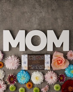 doTERRA Precious Florals Collection with the letters M O M surrounded by flowers on a gray stone background with space for your message.