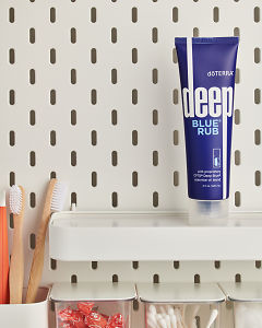 doTERRA Deep Blue Rub on a bathroom shelf with additional doTERRA products and bathroom accessories.