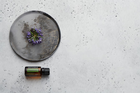 doTERRA Rosemary with rosemary flowers on a ceramic plate on a white concrete background.