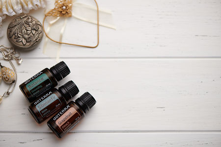 doTERRA Balance, Siberian Fir and Grapefruit oils and wedding accessories on white rustic wooden background.