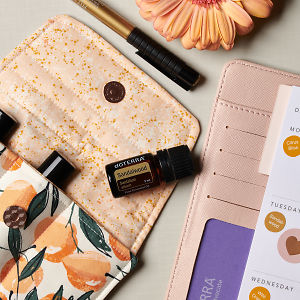 doTERRA Sandalwood on an essential oil bag with a flower, pen and diary on a white textured background.