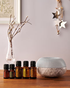 doTERRA Brevi Stone diffuser with Cinnamon, Douglas Fir, Citrus Bliss, Lemon and Wild Orange essential oils and holiday decorations on a side table.