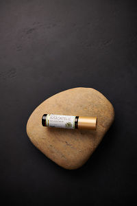 doTERRA Immortelle sitting on a stone on a black concrete background.