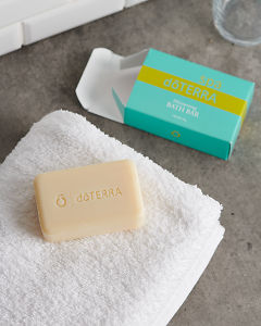 doTERRA Spa Moisturizing Bath Bar with a white fluffy towel on a stone bathroom bench top.