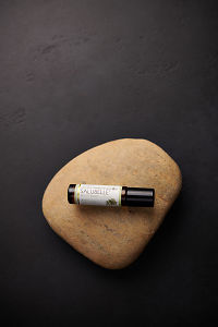 doTERRA Salubelle sitting on a stone on a black concrete background.