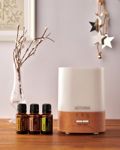 doTERRA Lumo diffuser with Citrus Bliss, Grapefruit and Lime essential oils and holiday decorations on a side table.
