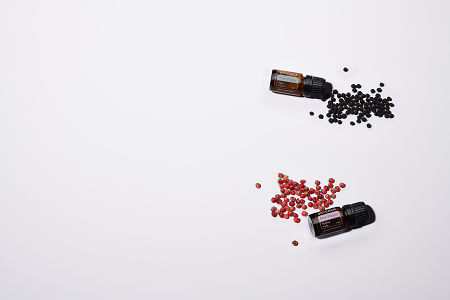 doTERRA Black Pepper and Pink Pepper with black and pink peppercorns on a white background.