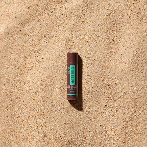 doTERRA Spa Herbal Lip Balm in direct sunlight on the beach.