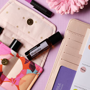 doTERRA Magnolia Touch on an essential oil bag with a pink flower and diary on a pale pink textured background.