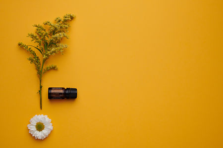doTERRA Motivate with flowers and leaves on an orange card stock background.