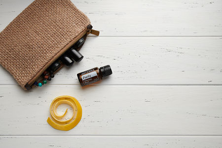 doTERRA Purify, lemon peel and clutch with oils on white wooden background.
