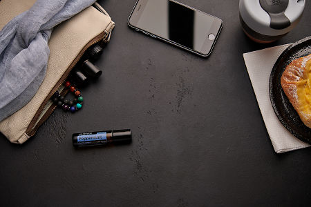 doTERRA Peppermint Touch with a leather clutch, roller bottles, cell phone, coffee and food on a black background.