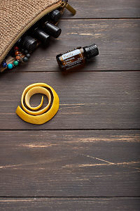 doTERRA Purify, lemon peel and clutch with oils on brown wooden background.