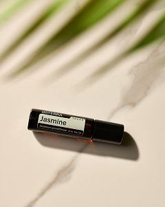 doTERRA Jasmine Touch in sunlight on a marble table.