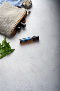 doTERRA Easy Air Touch with clutch, accessories and mint leaves on a white concrete background.