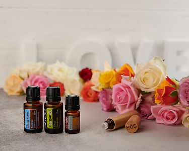 doTERRA Ylang Ylang, Bergamot and Black Pepper with a bamboo roller bottle and roses on a concrete bench top.
