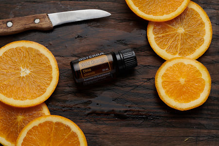 doTERRA Wild Orange oil, orange slices and knife on rustic wooden chopping board.