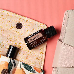 doTERRA Grapefruit on an essential oil bag with a pink diary  on a coral pink textured background.