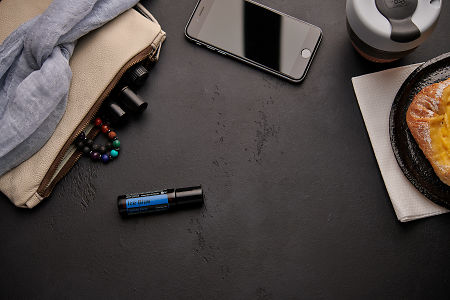doTERRA Ice Blue Roll On with a leather clutch, roller bottles, cell phone, coffee and food on a black background.