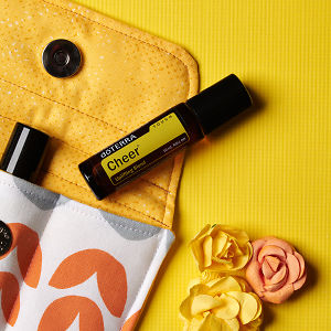 doTERRA Cheer Touch on an essential oil bag with scattered flowers on a yellow textured background.