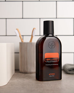 doTERRA On Guard Mouthwash and bathroom accessories on a bathroom vanity.