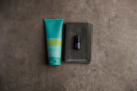 doTERRA Spa Hand and Body Lotion with Blue Tansy essential oil on a gray washcloth on a stone background.