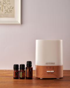 doTERRA Lumo diffuser with Arborvitae, Cardamom and Cassia essential oils on a side table.
