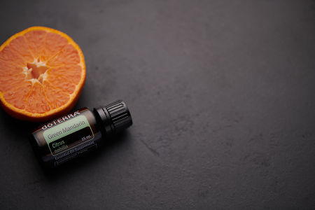 doTERRA Green Mandarin oil and mandarin slice on black concrete background.