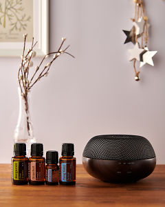 doTERRA Brevi Walnut diffuser with Bergamot, Grapefruit, Juniper Berry and Ylang Ylang essential oils and holiday decorations on a side table.