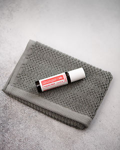 doTERRA Stronger on a gray washcloth on a concrete background.