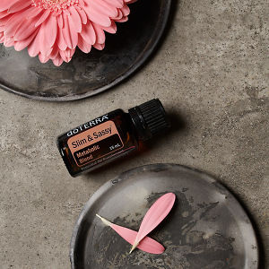 doTERRA Slim and Sassy essential oil with pink flowers and  petals on ceramic plates on a grey stone background.