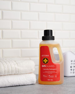 doTERRA On Guard Laundry Detergent on a laundry bench with a white tiled background.