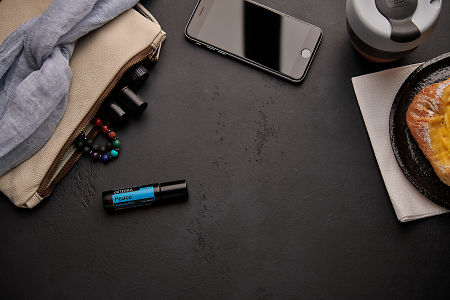doTERRA Peace Touch with a leather clutch, roller bottles, cell phone, coffee and food on a black background.