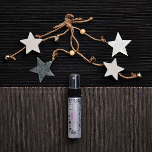 doTERRA Serenity Linen Mist with holiday decorations on a dark gray and medium gray textured background.