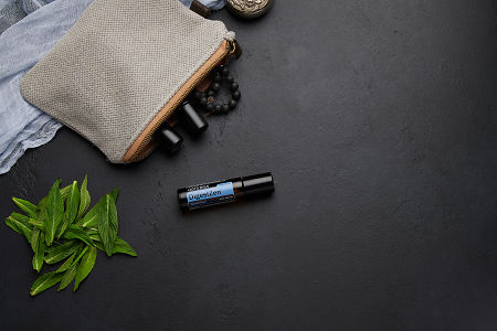 doTERRA DigestZen Touch with clutch, accessories and mint leaves on a black concrete background.