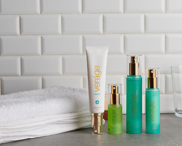 doTERRA Verage Skin Care Collection with a white fluffy towel on a gray stone bathroom bench top.
