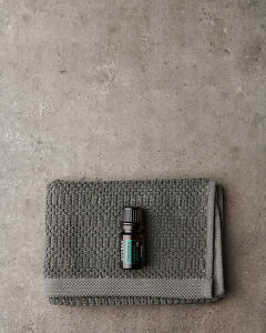 doTERRA Ravintsara on a washcloth on a gray stone background.