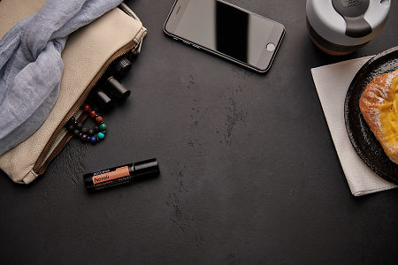 doTERRA Neroli Touch with a leather clutch, roller bottles, cell phone, coffee and food on a black background.